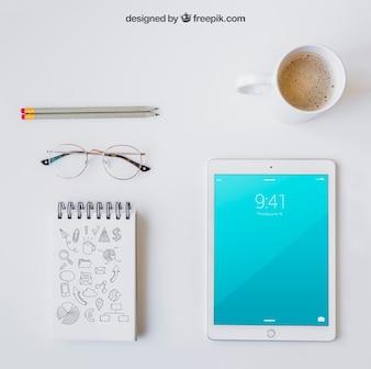 Occhiali, notebook, matite, tavoletta e caffè