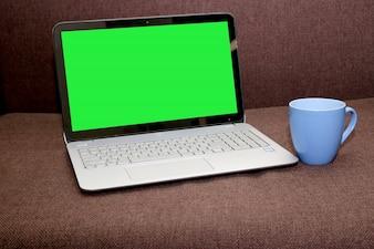 Schermo del computer portatile in bianco con una tazza di tè su sfondo marrone