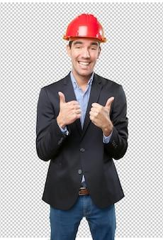 Glücklicher junger Architekt mit Daumen nach oben