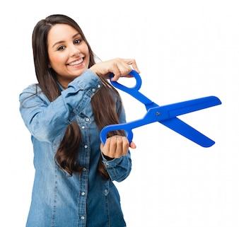 Junge Frau, die eine blaue Kunststoff-Schere halten