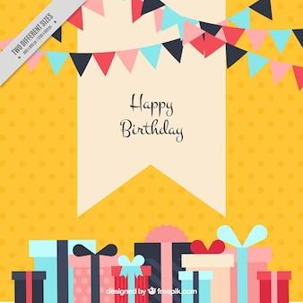 Fond jaune avec des guirlandes et des cadeaux d'anniversaire