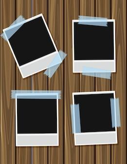 Quatre photoframes vierges sur planche de bois
