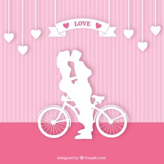 Silhouettes d'un couple embrassant sur un vélo