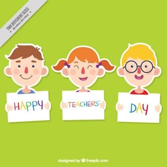 Alumnos sonrientes sujetando carteles para el día del profesor