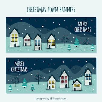 Banners de feliz navidad con casas dibujadas a mano