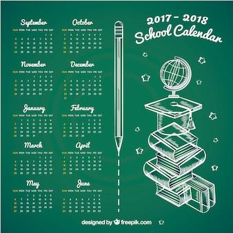 Calendario escolar a mano sobre pizarra