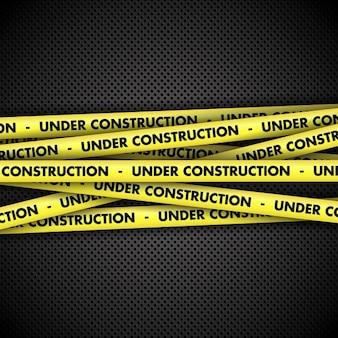 Cinta de advertencia de en construcción en fondo metálico
