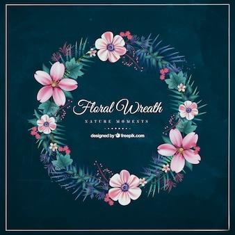 Corona floral decorativa con flores en tonos rosas