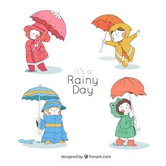 Cuatro niños adorables con paraguas dibujados a mano