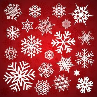 Diferentes copos de nieve sobre un fondo rojo