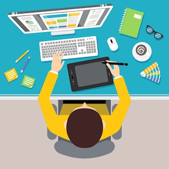 Diseñador de lugar de trabajo con vista superior hombre sentado en la mesa con monitor y herramientas de dibujo ilustración vectorial