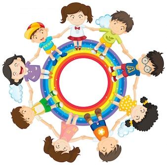 Felices los niños de la mano alrededor del círculo del arco iris