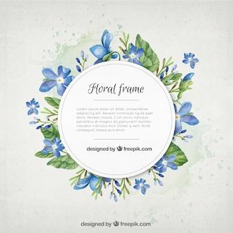 Flores de color azul de la acuarela con el marco de las hojas