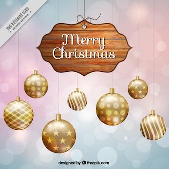 Fondo bokeh con cartel de navidad y bolas doradas