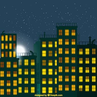 Fondo de ciudad de noche con ventanas iluminadas