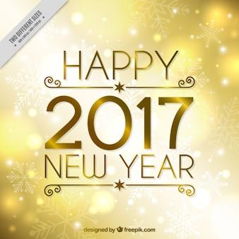 Fondo dorado de año nuevo con copos de nieve
