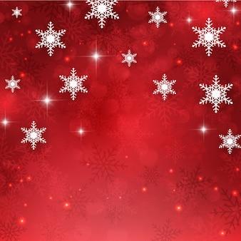Fondo rojo resplandeciente con copos de nieve