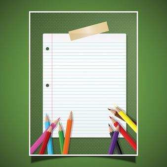 Fondo verde con un papel y lápices de colores