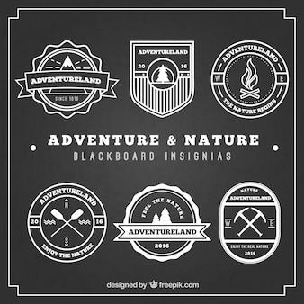 Insignias de aventuras y naturaleza en pizarra