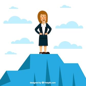 Mujer de negocios sonriente en la cima de una montaña