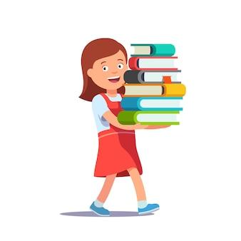 Niña linda de la escuela que lleva la pila grande de libros