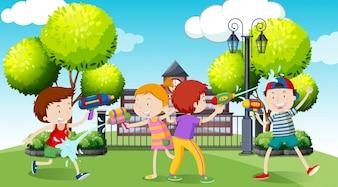 Niños jugando pistola de agua en el parque ilustración