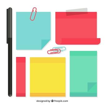 Notas adhesivas coloridas con algunos clips y bolígrafo