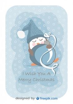 Pingüino durmiendo con una pelota de Navidad