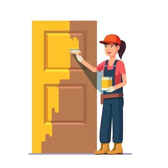 Pintor profesional pintando la puerta en color amarillo