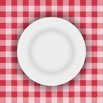 Plato blanco en un paño de mesa de picnic