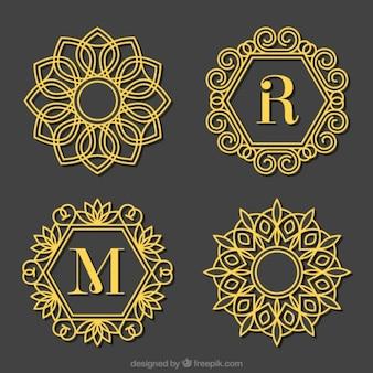 Set de logos de letras mayúsculas ornamentales doradas