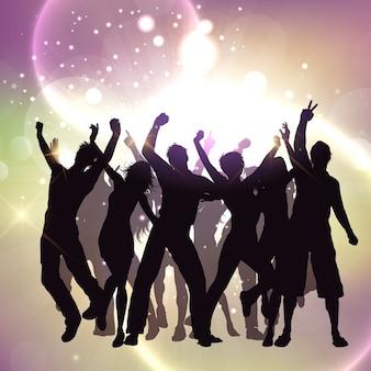 Siluetas de gente bailando sobre un fondo brillante