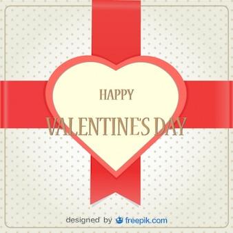 Tarjeta con corazón de San Valentín sobre cinta de regalo