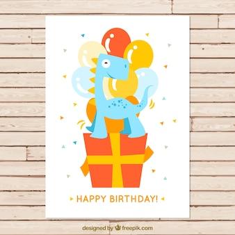 Tarjeta de cumpleaños de simpático dinosaurio encima de un regalo
