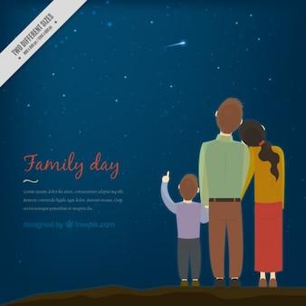 Tarjeta de familia adorable observando las estrellas