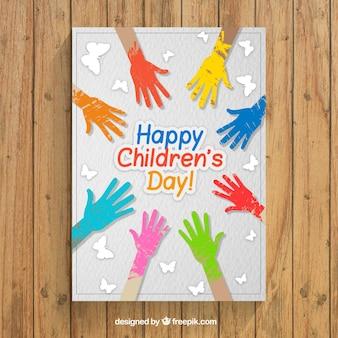 Tarjeta de felicitación del día del niño con manos de pintura de colores