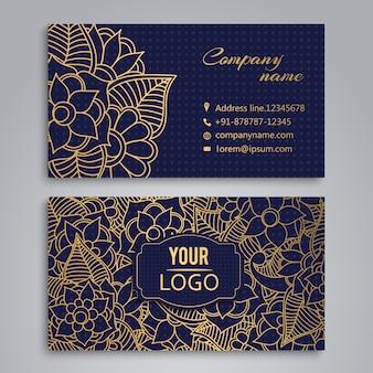 Tarjeta de presentación con diseño de flores doradas sobre fondo azul
