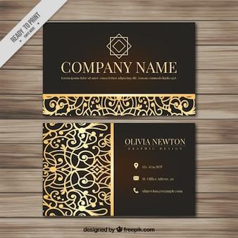 Tarjeta ornamental de negocio con detalles dorados