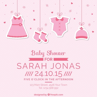 Tarjeta rosa de bienvenida del bebé con ropa colgando