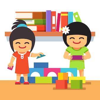 Asiatische Kinder spielen Gebäude Turm zusammen