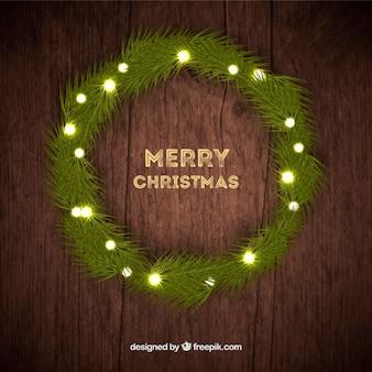 Beleuchtete Weihnachtskranz auf Holz Hintergrund