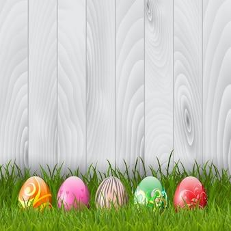 Dekorative Ostereier im Gras auf einem hölzernen Hintergrund