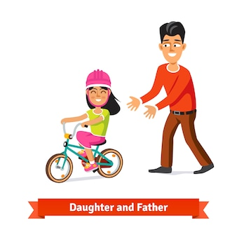 Vater lehrt Tochter, ein Fahrrad zu fahren