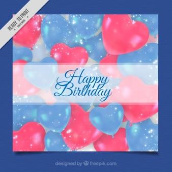balões vermelhos do coração azul e cartão de aniversário