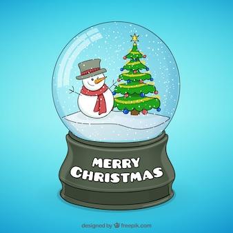 Boneco de neve e árvore de Natal dentro de uma bola de cristal