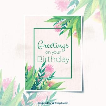 Cartão de aniversário com folhas da aguarela e flores