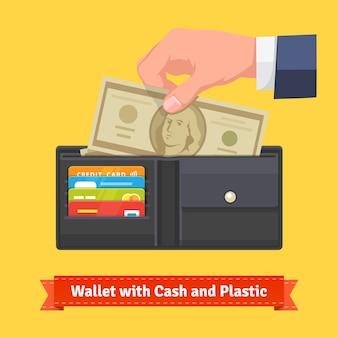 Carteira de couro com alguns dólares e cartões de crédito