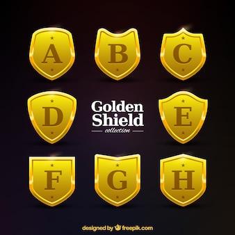 Coleção de escudos de ouro com letras maiúsculas