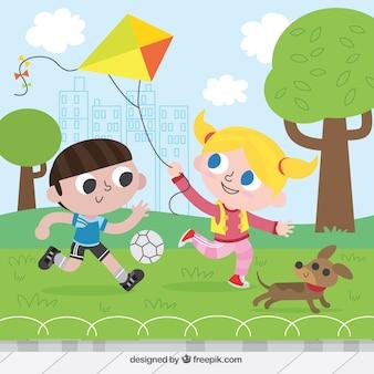 Crianças felizes que jogam com papagaio e bola