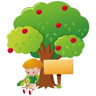 Escrita do menino debaixo de uma árvore